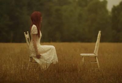 mujer mirando silla vacía